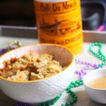 Cafe au Lait Bread Pudding in a white bowl with an orange rim next to a small white bowl of cafe au lait sauce, all surrounded by mardi gras beads, with a Cafe du Monde coffee can in the background