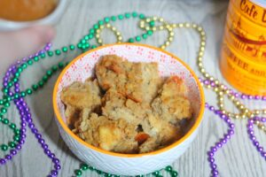 Cafe au Lait Bread Pudding in a white bowl with an orange rim surrounded by mardi gras beads with a Cafe du Monde coffee can in the background
