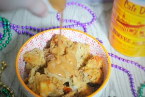 Cafe au Lait Bread Pudding in a white bowl with an orange rim surrounded by mardi gras beads, and a stream of cafe au lait sauce pouring onto it, with a Cafe du Monde coffee can in the background