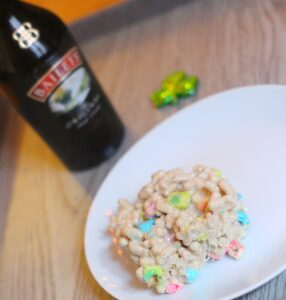 A bar made out of lucky charms and bailey's marshmallows on a round white plate with a bottle of baileys and a green shamrock in the background