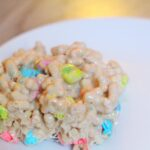 A bar made out of lucky charms and bailey's marshmallows on a round white plate