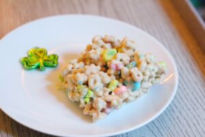 A bar made out of lucky charms and bailey's marshmallows and a green shamrock on a round white plate