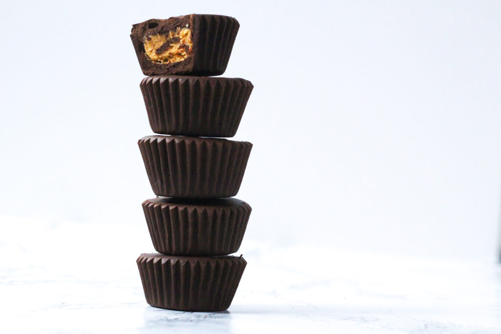 side view of a stack of 5 peanut butter cups with a bite taken out of the top one and the peanut butter filling exposed. The stack is surrounded by a white background.