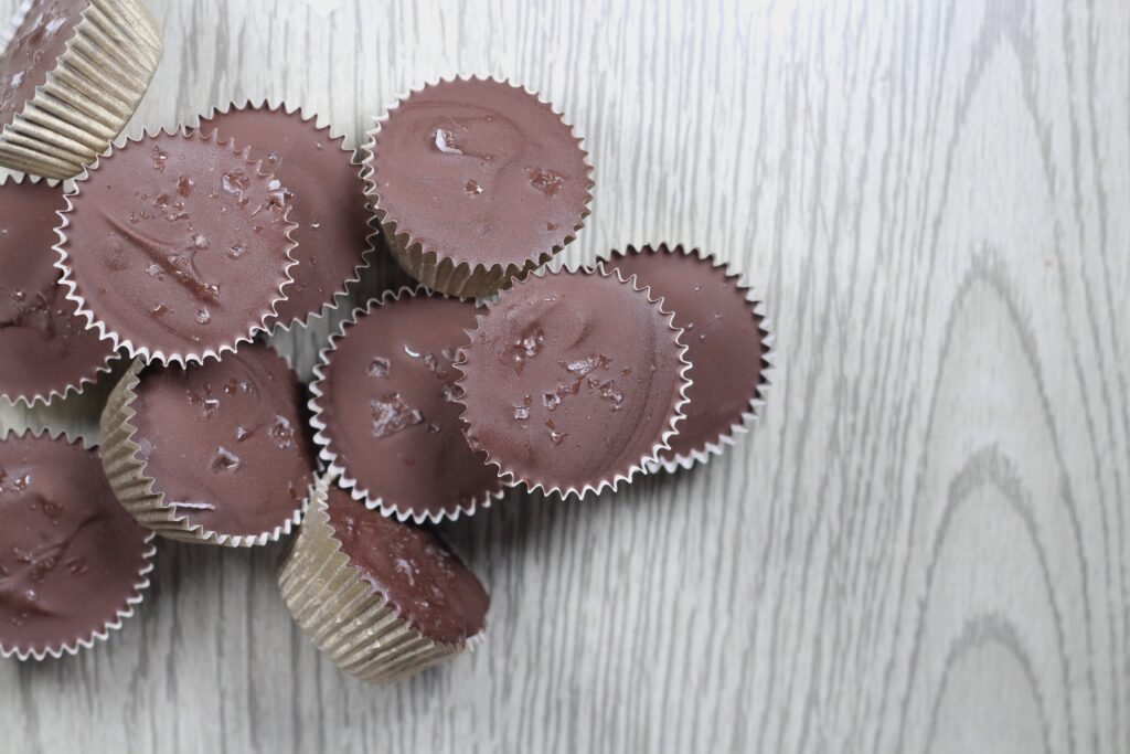 Pile of Nutella cups in gold paper wrappers topped with sea salt flakes