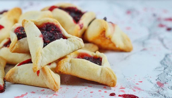 A pile of sangria hamentaschen sangria hamentashen on a white marble surface with spatters of filling on the marble