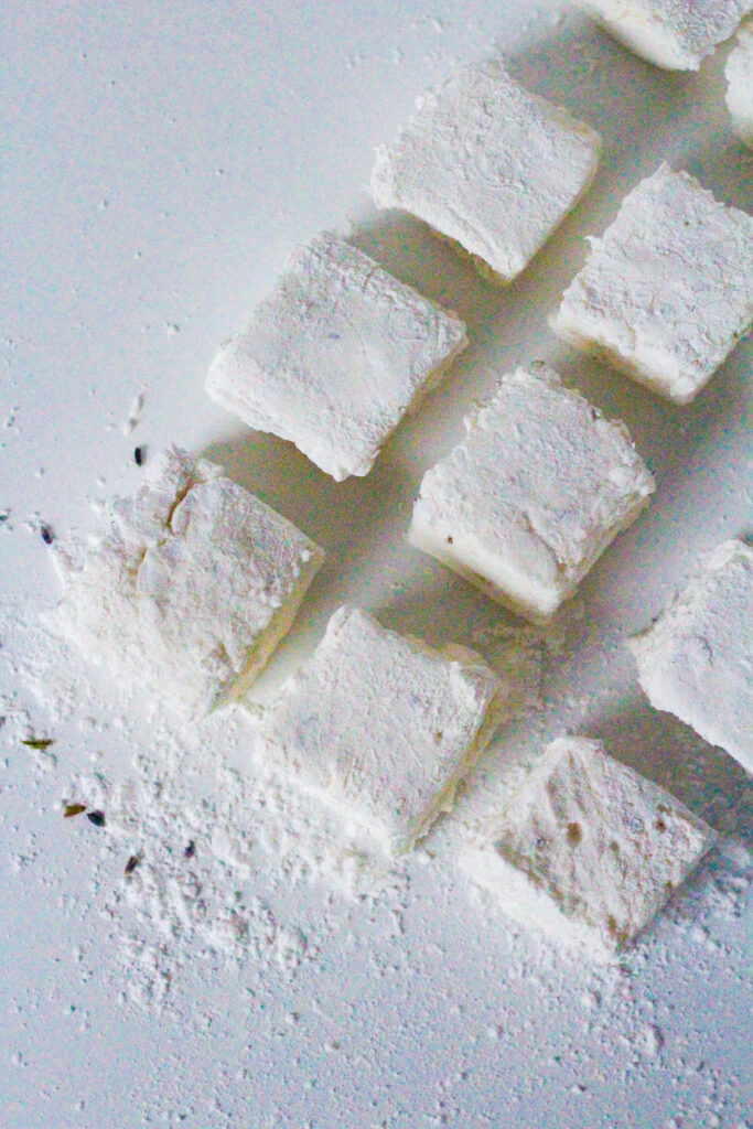 top down view of lemon lavender marshmallows arranged in a rectangular pattern with a bit of space between each marshmallow.  The rectangle of marshmallows is coming into the frame from the top right corner at an angle so that going from the midleft side of the frame up to the top right side of the frame you can see three and a piece of a fourth marshmallows forming the left side of the rectangle.  From that same center left marshmallow going down to the bottom right of the frame there are two more marshmallows forming the shorter bottom side of the rectangle. The center left marshmallow is surrounded by powdered sugar, corn starch, and lavender.