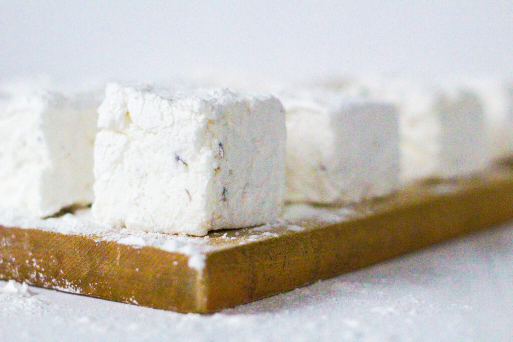 side view of lemon lavender marshmallows arranged in a rectangular pattern on top of a wooden cutting board.  The image focuses on the corner of the marshmallow in the bottom right corner of the cutting board, which is sitting at an angle in the frame. the remaining marshmallows are blurred in the background and going out of the frame.