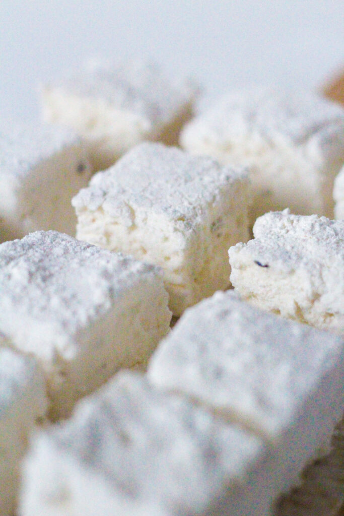Close up of lemon lavender marshmallows from a 45 degree angle view. One marshmallow in the middle of others is clear and the others are blurred.