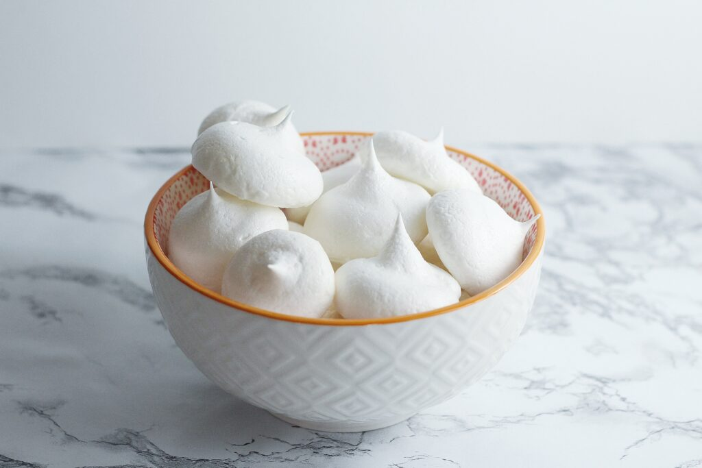White textured bowl with orange rim filled with white meringues in front of a white background on a marbled surface