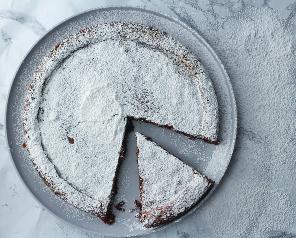 top down view of flourless chocolate cake covered in powdered sugar with one piece sitting in the open space where a bigger slice was removed