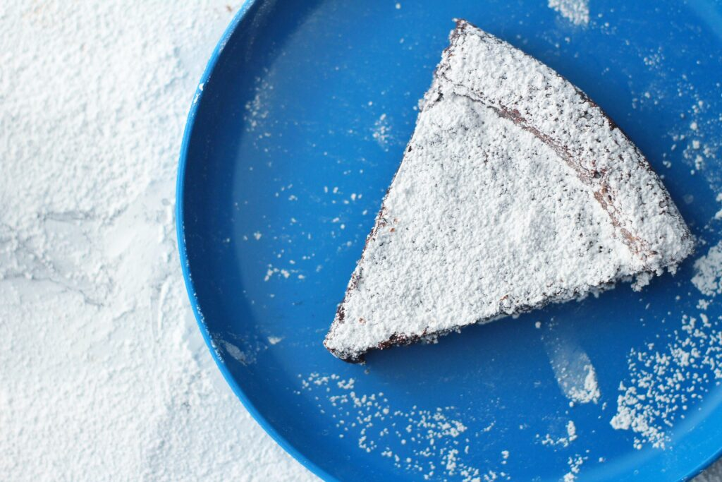 Slice of flourless chocolate cake on a round blue plate on top of a marbled surface covered in powdered sugar
