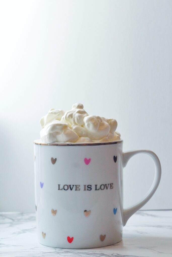 A white mug with a gold rim covered in multi-colored hearts that says love is love on the front with Bailey's whipped cream sitting on top