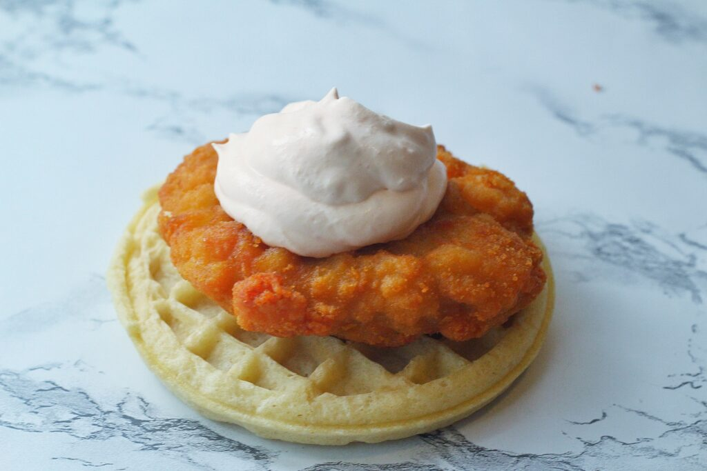 A waffle sitting on a marbled surface topped with a piece of fried chicken topped with whipped sriracha