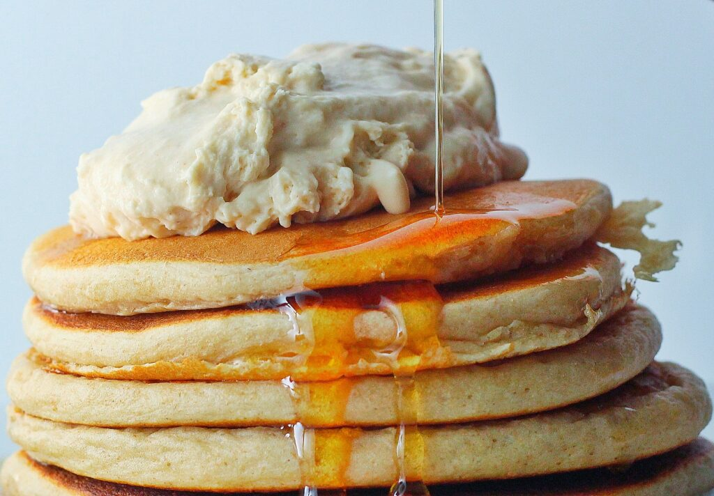 Whipped Peanut Butter piled on top of a stack of pancakes with a stream of maple syrup flowing down the side of the pancake stack