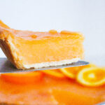 Side view of a slice of aperol spritz pie being held on a pie server above the rest of the aperol spritz pie. All on a white surface in front of a white background.