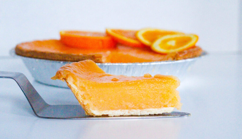Side view of a slice of aperol spritz pie on a pie server sitting in front of the rest of the aperol spritz pie. All on a white surface in front of a white background.