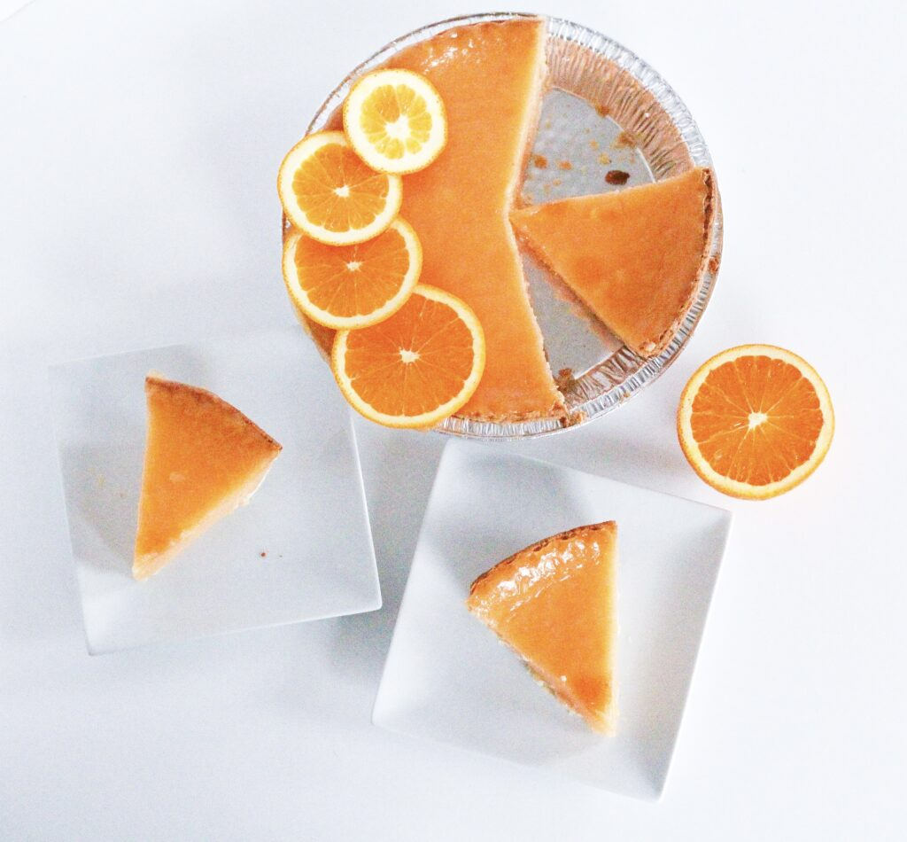 Top down view of the pie with three slices cut. One slice is in the open space in the pan where other slices have been removed. The other two slices are each on a small square white plate. There is also half an orange sitting next to the pie.