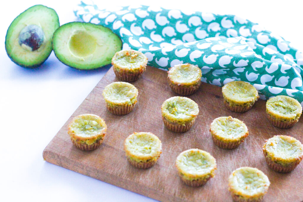 Angled view of avocado cheesecakes on a brown wooden cutting board sitting on a white surface. To the top left of the cutting board is two halves of an avocado, and to the right of the avocado is a green patterned cloth napkin.