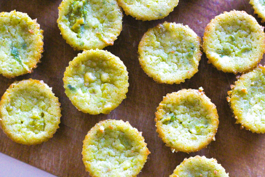 Close up top down view of avocado cheesecakes on a wooden cutting board