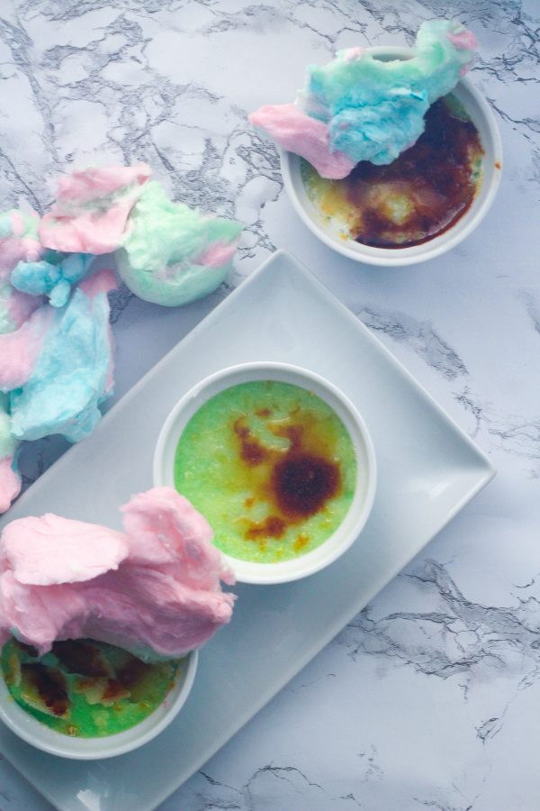 Top down view of two cotton candy creme brulees in the bottom left corner of the photo on a rectangular white plate, one of which has pink cotton candy of top of it. above the plate along the left hand side of the image is blue and pink cotton candy. In the upper right corner is another cotton candy creme brulee with pink and blue cotton candy on top of it. All on top of a white marbled surface.
