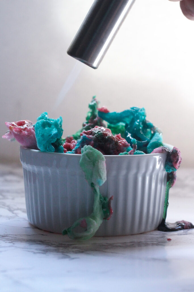 Side view of a white, ribbed ramekin with melting pink, blue, and green cotton candy on top, with a torch above it and a flame melting the cotton candy topping.