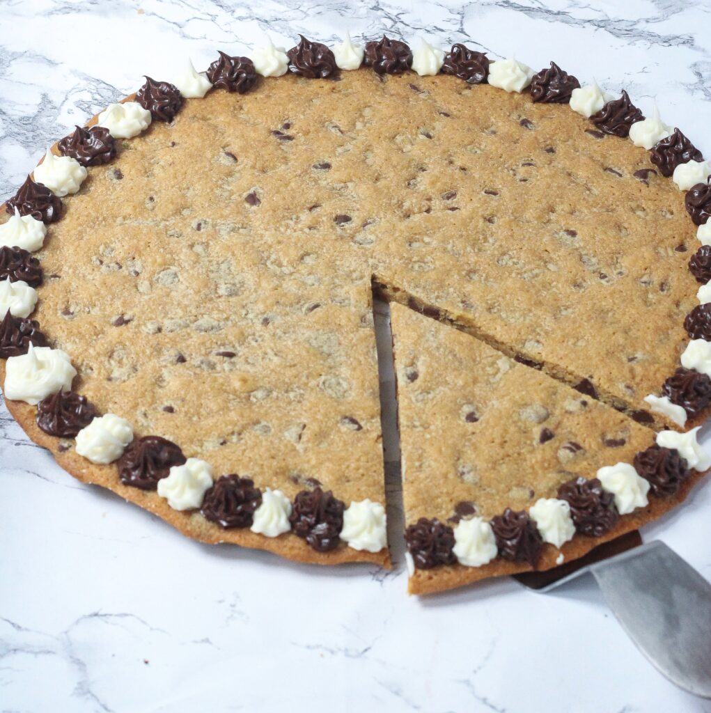 angled shot of a chocolate chip cookie cake with alternating brown and white frosting flowers around the outside of the cookie, with a slide in the bottom right of the cookie cut and sitting on a cake server, pulled slightly out, on a marbled surface
