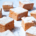 Angled view of pumpkin spice marshmallows spread around on a white marble surface