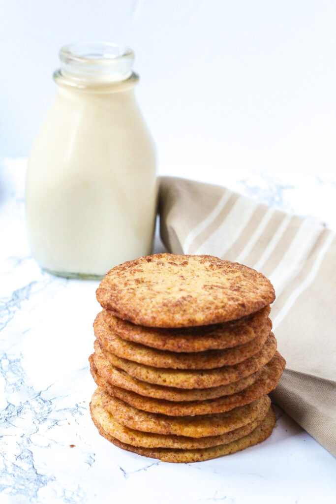 Stack of French Toast Cookies in front of a glass container of milk, with a beige napkin with some white stripes on it to the right