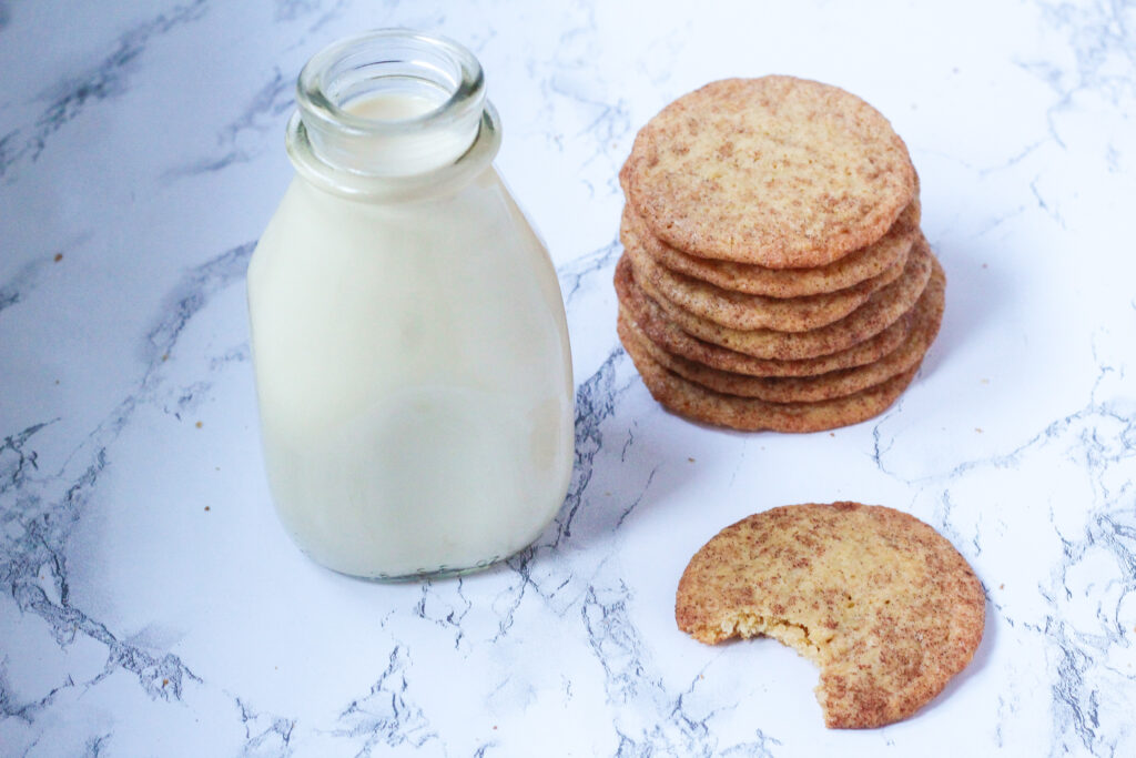 Stack of french toast cookies to the right of a glass milk jar, with a cookie with a bite out of it in front of the cookie stack, all on a marbled surface