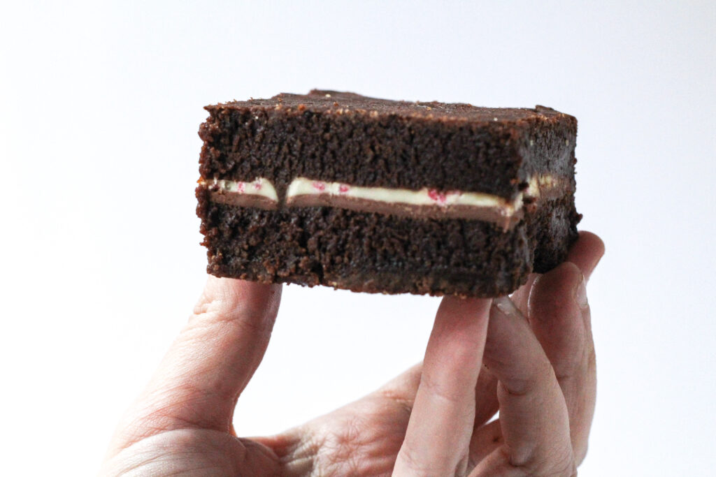 A hand in the bottom of the frame, cupped with the fingers pointing upwards holding a brownie on top of the fingers. The Peppermint mocha brownies are dark brown brownies with a thin strip of white in the center from the peppermint bark square