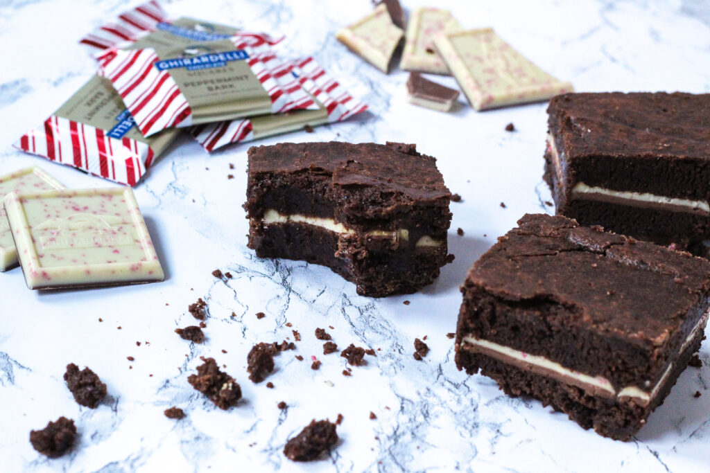 angled view, with a brownie with a bite taken out of it in the center of the frame. to the left of the brownie is whole, unwrapped peppermint bark squares, some wrapped peppermint bark squares in the top left corner. Top center, behind the brownie, is broken pieces of peppermint bark squares. Along the right side of the frame is two more brownies. In front of the bitten brownie at the bottom of the frame is a bunch of brownie crumbs.