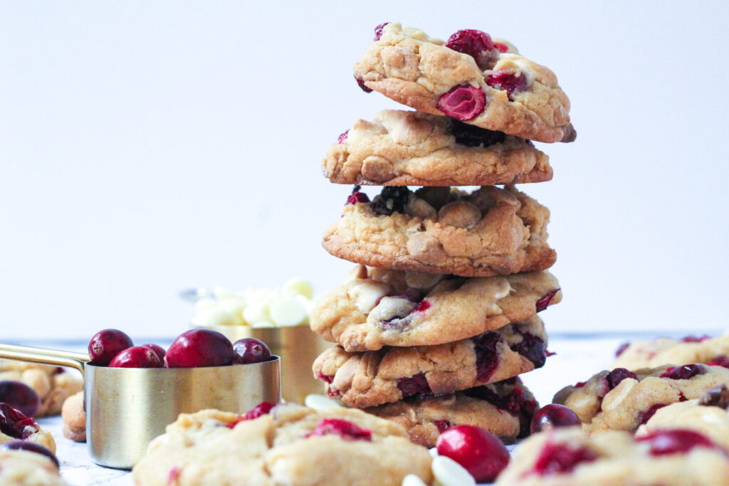 A stack of cranberry white chocolate chip cookies surrounded by a single layer of cookies. To the left of the stack are two gold measuring cups, one filled with cranberries and one with white chocolate chips.