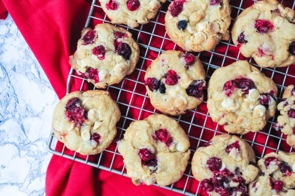 top down view of cranberry white chocolate chip cookies on a wire rack sitting on a red napkin with the white marble surface underneath showing on the left side of the frame