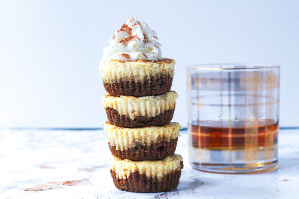 A side view of a stack of four eggnog cheesecakes topped with whipped cream and a sprinkle of cinnamon. to the right and set slightly back is a clear glass with a plaid pattern in gold, with brown bourbon filling about a third of the glass.