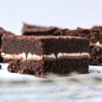 Close up side view of a peppermint mocha brownie, with other peppermint mocha brownies blurred in the background. The brownie in focus is at an angle so the corner is facing the camera. The peppermint mocha brownies are dark brown brownies with a thin white layer in the center from the peppermint bark square