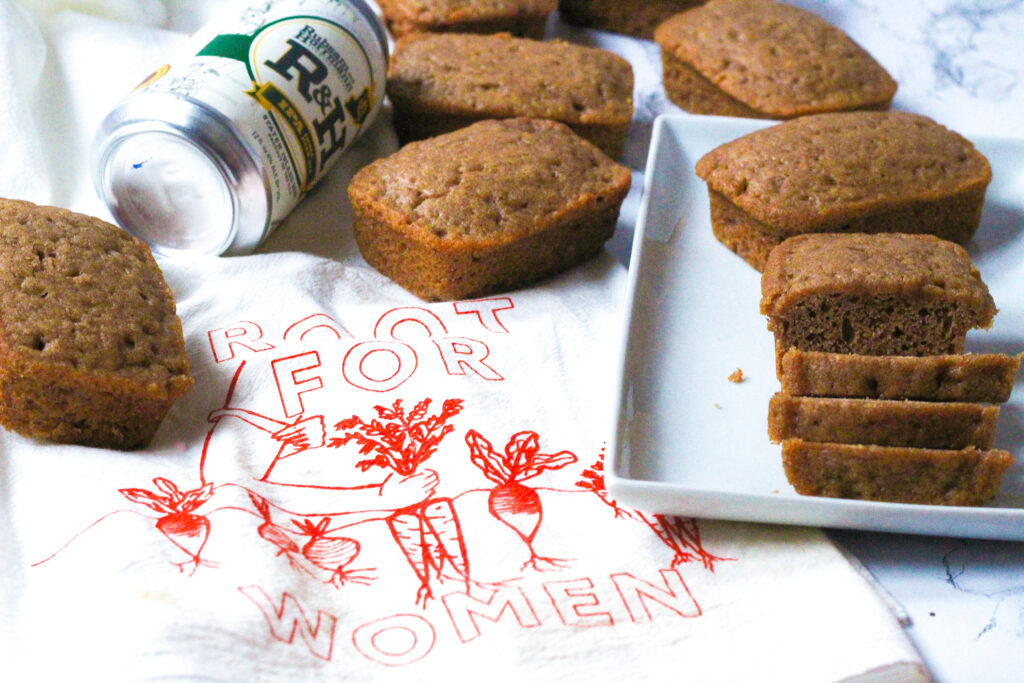On the left side of the photo is a white dish towel that says Root for Women in red with root vegetables on it. In the upper left of the image on top of the towel above the words are some mini loaves of spiced beer bread and a can of R&H IPA Beer. On the right side of the photo is a white rectangular plate that slightly overlaps the towel. On the plate in the back is a mini loaf, and in the front is a loaf, the front half of which is sliced into three slices.
