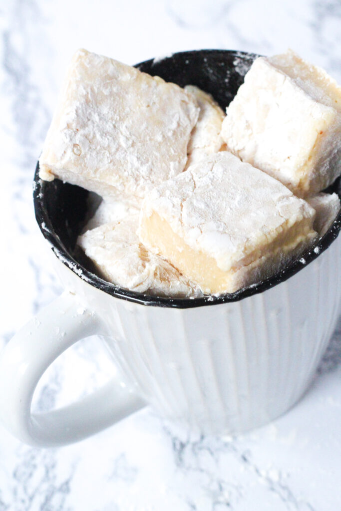 An angled top-down view of a mage that is white and textured on the outside and black on the inside, filled with Bailey's Marshmallows. The mug sits on a white marbled surface.