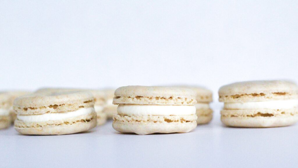 Side view of Oatmeal Cream Pie Macarons. Three macarons are visible in the shot, with a few more peeking out from behind.
