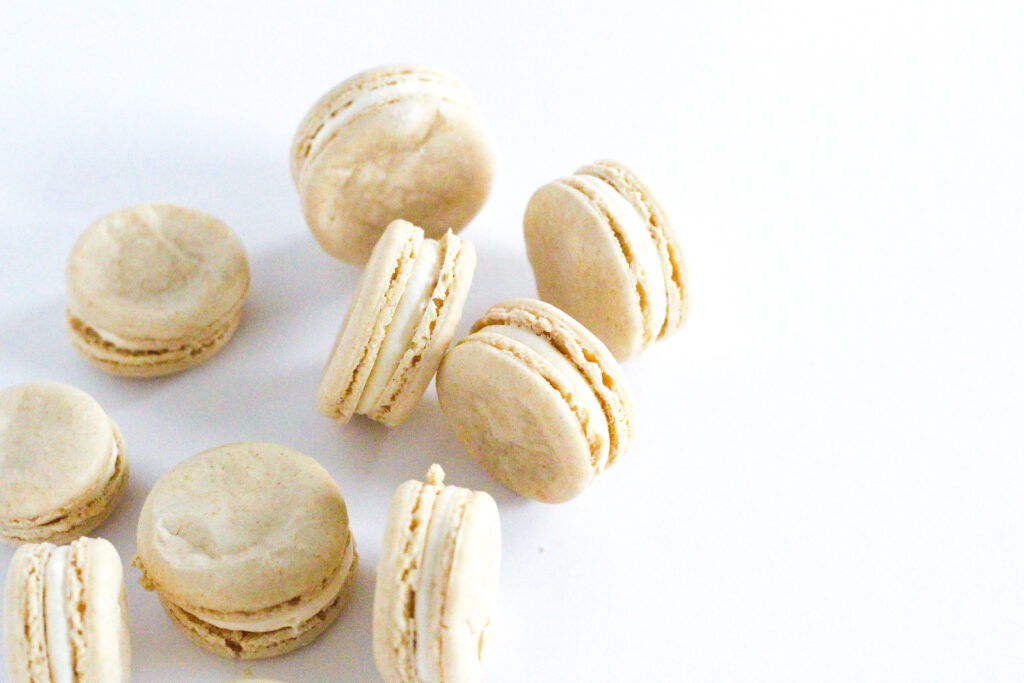 Oatmeal cream pie macarons, some standing on their edges, coming into the shot from the left side of the frame