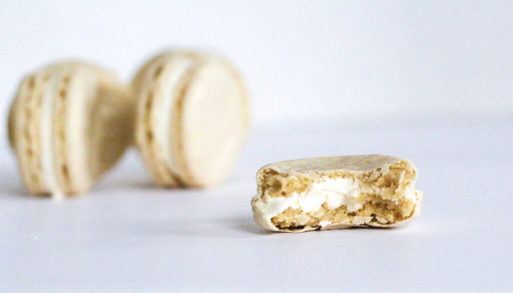 Photo of the inside of an oatmeal cream pie macaron with a bite taken out of it, with whole macarons standing on their edges in the background to the left of the frame.