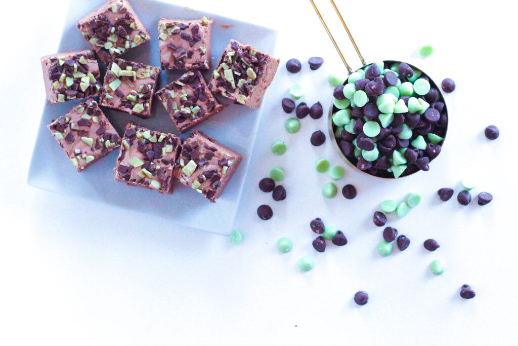 Top down view of a white square plate with mint chocolate chip fudge on it on the left side of the frame.  On the right size of the frame is a gold measuring cup filled with mint and chocolate chips which have overflowed out of the cup on to the white surface.