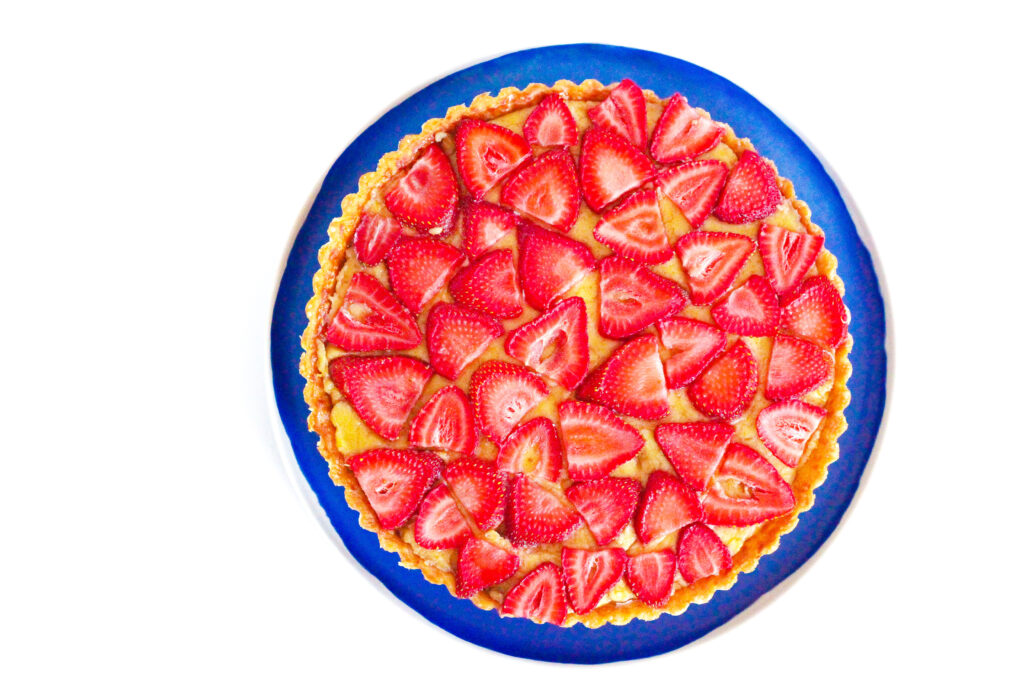 Top down view of a balsamic strawberry & basil tart on a blue plate on a white surface