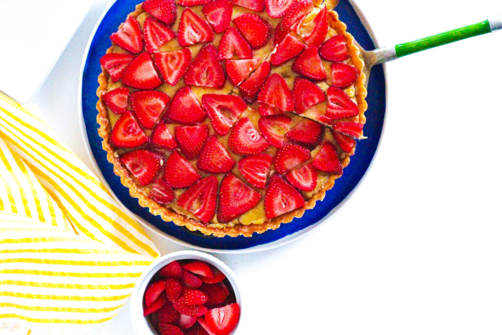 Top down view of a strawberry balsamic tart with the tart cut off of the top of the frame. A slice is cut out of the tart with a pie server under it, the green handle of the pie server sticking out to the right of the frame. below the tart is a small bowl of sliced strawberries, and to the left is a yellow striped towel.  The tart is on a blue plate, and the scene is on a white surface.
