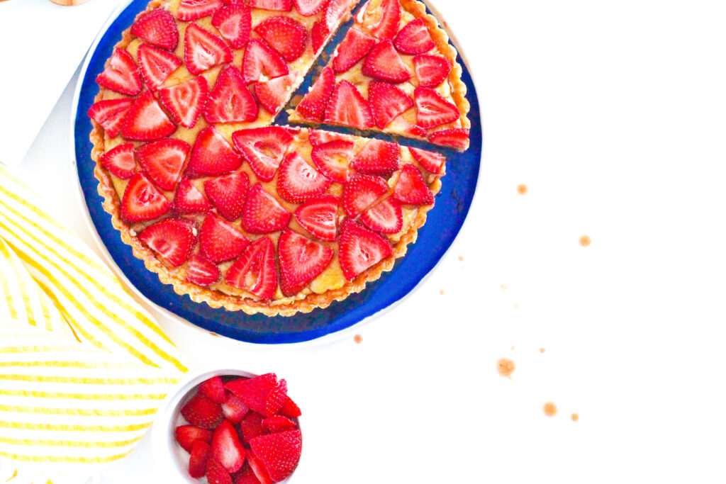 A slice slightly shifted out of a balsamic strawberry and basil tart with a bowl of strawberries below the tart and a yellow striped napkin to the left of the tart. To the right of the frame are splatters of balsamic on a white surface.