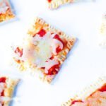 Top down view of pizza poptarts on a white surface. A square poptart is in the center, and all the poptarts surrounding it are partially out of the frame on all sides.