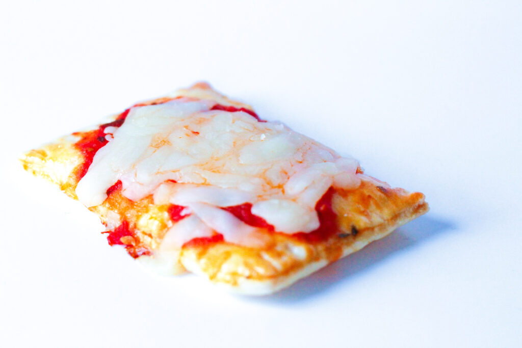 Close up of a pizza poptart on a white  surface. A golden flakey crust with fork imprints around the edges, topped with red pizza sauce and white mozzerella cheese