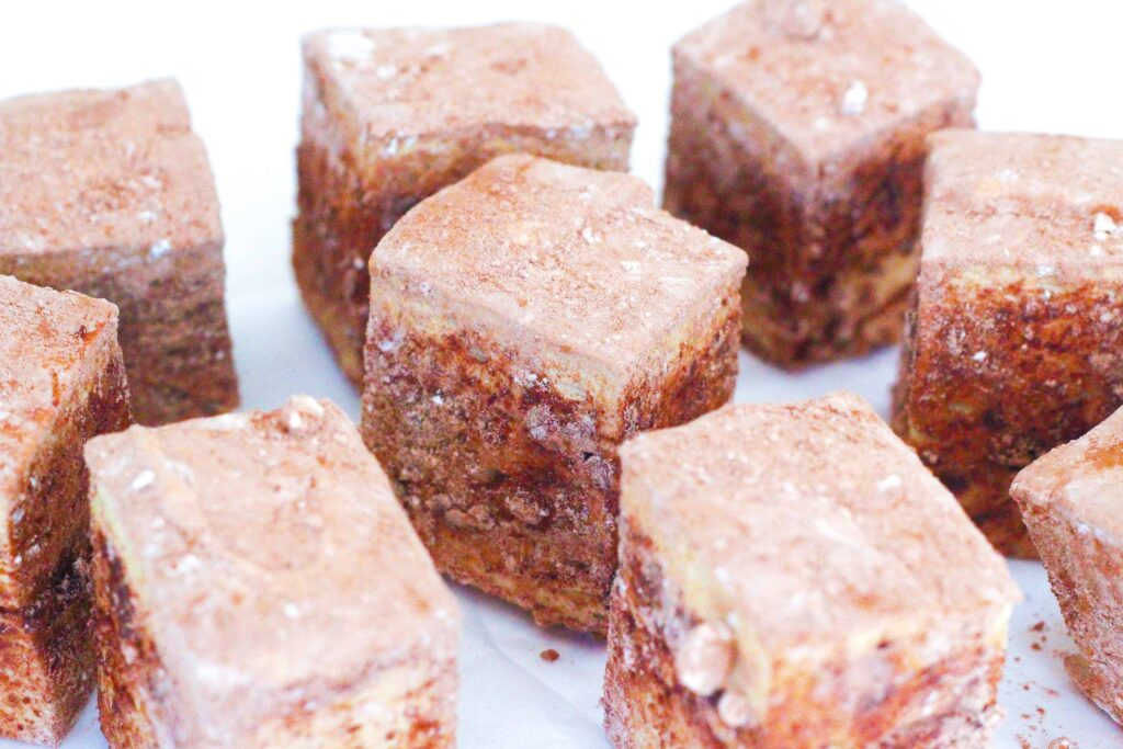 Angled view of coffee marshmallows off kilter on a white surface