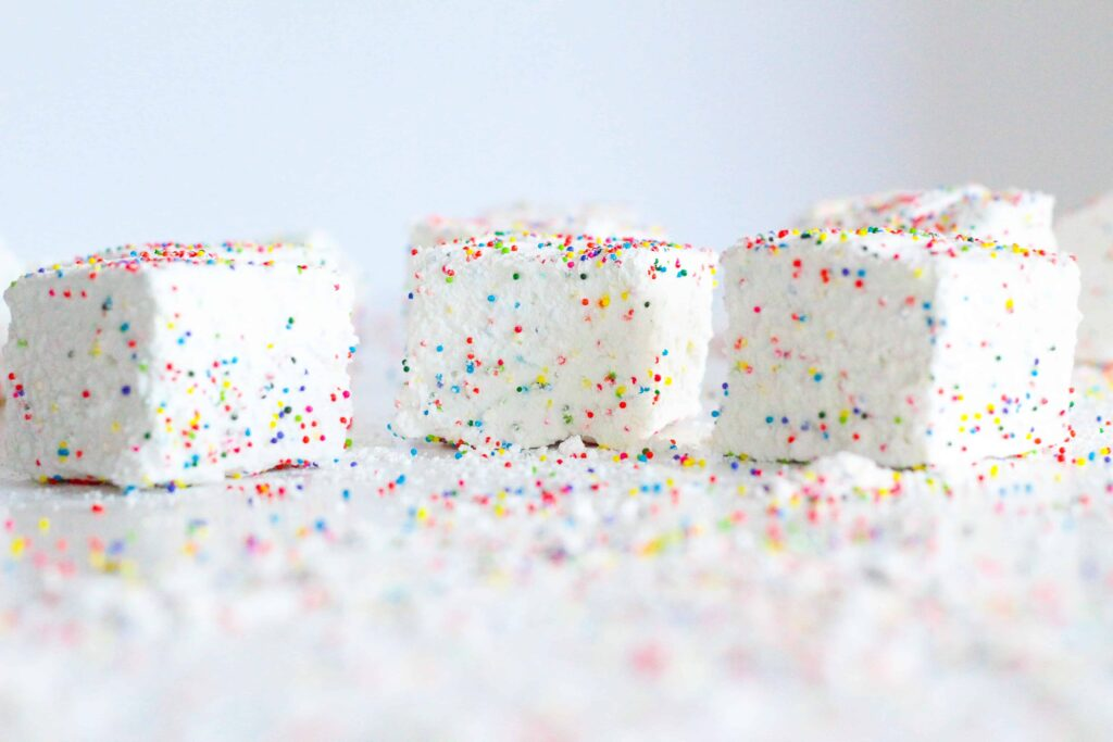 side view of three birthday marshmallows on a white surface with extra sprinkles everywhere
