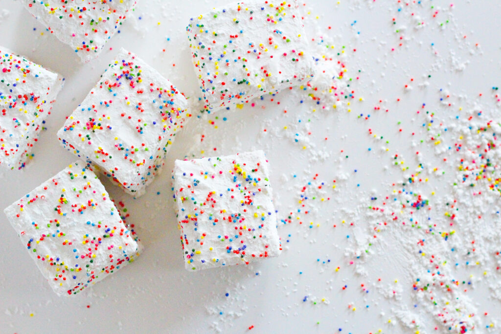 top down view of birthday marshmallows in the left hand side of the frame with excess cornstarch sprinkle coating on the right hand side of the frame. All on a white surface.