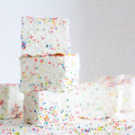 stack of 3 birthday marshmallows surrounded by other marshmallows and lots of sprinkles on a white surface